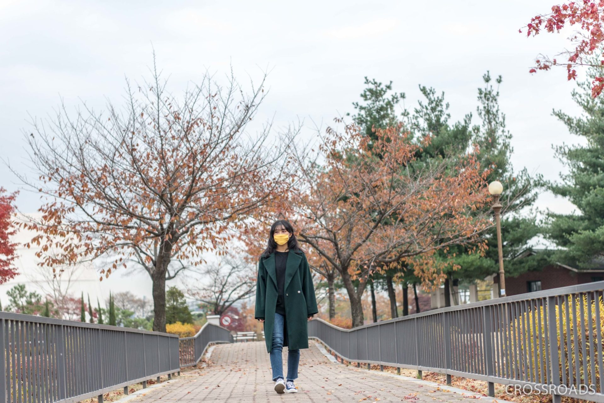 YuJin walks along the autumnal trees.